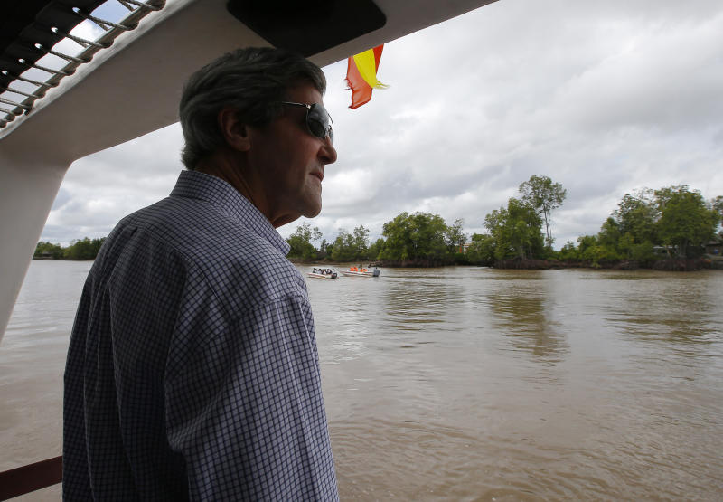 U.S. Secretary of State John Kerry rides a boat through the Mekong River Delta Sunday, Dec. 15, 2013. Along the winding muddy waters of the Mekong Delta where he once patrolled for communist insurgents on a naval gunboat, Secretary of State Kerry turned his sights Sunday on a new enemy: climate change. (AP Photo/Brian Snyder, Pool)