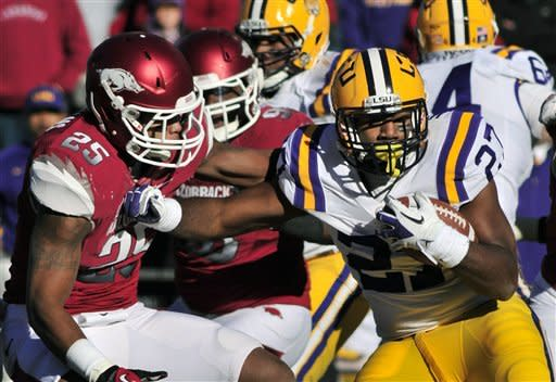 LSU running back Kenny Hilliard (27) carries the ball past Arkansas linebacker Terrell Williams (25) during the first half of an NCAA college football game in Fayetteville, Ark., Friday, Nov. 23, 2012. (AP Photo/April L. Brown)