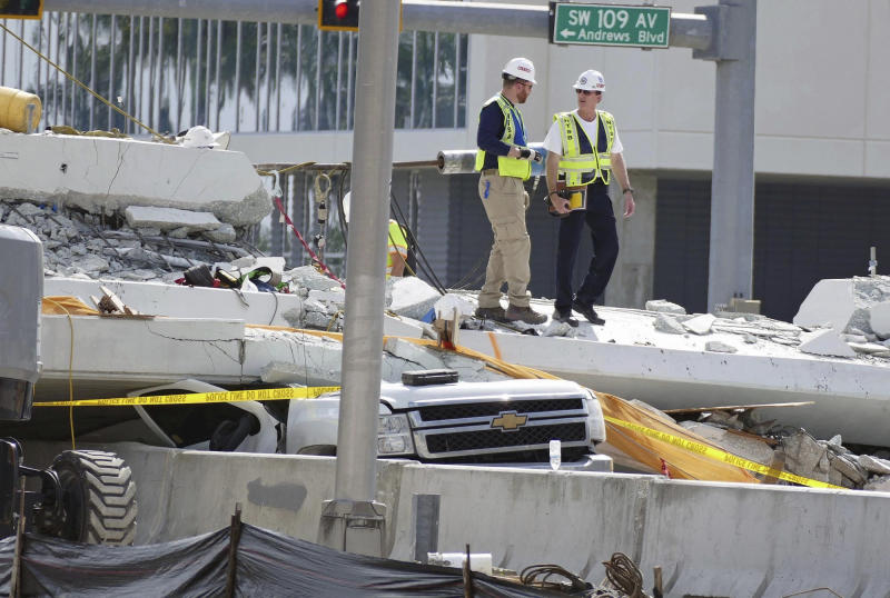 FILE - In a Sunday, March 18, 2018 file photo, inspectors walk over what remains of a pedestrian bridge near Florida International University, near Miami. Federal investigators said  in the two-page investigative update released Thursday, Nov. 15, 2018, that design flaws caused cracking in a pedestrian bridge that collapsed near Miami in March. The National Transportation Safety Board did not blame those errors for the March 15 collapse. Six people died in the collapse. (C.M. Guerrero/The Miami Herald via AP, File)