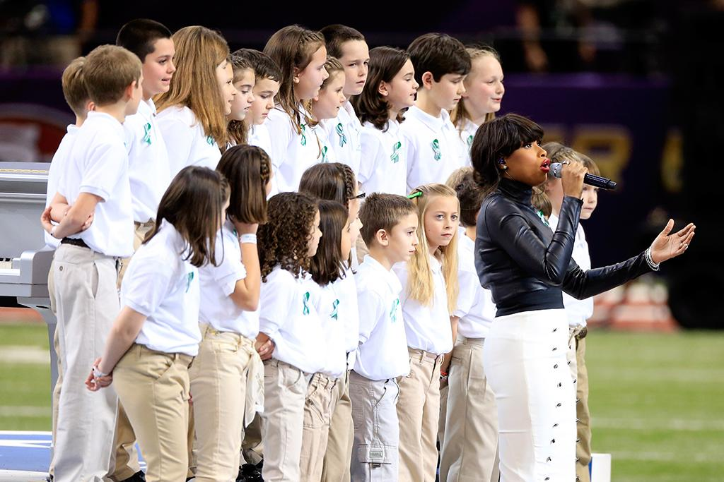 """Jennifer Hudson performs """"America The Beautiful"""" with the Sandy Hook Elementary School Chorus prior to the start of Super Bowl XLVII between the San Francisco 49ers and the Baltimore Ravens at the Mercedes-Benz Superdome on February 3, 2013 in New Orleans, Louisiana.  (Photo by Jamie Squire/Getty Images)"""