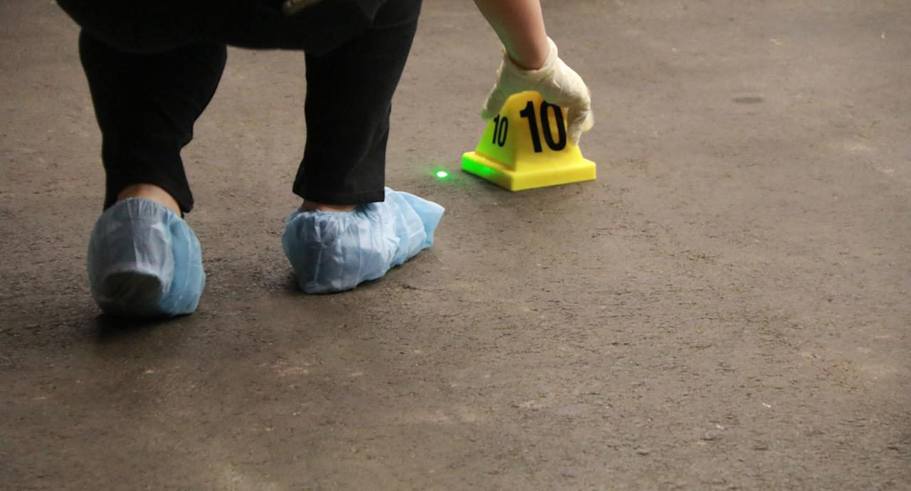 <p>Course participants during the Shooting Reconstruction Workshop put markers on the floor to indicate the position of bullet casings at the 'crime scene'.<br /> Photo: Hannah Teoh/Yahoo News Singapore </p>