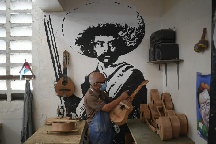 """A mural of Mexican revolutionary hero Emiliano Zapata decorates the Jacinto Perez lutherie school where Jose Luis Reyna teaches students to build their own traditional Venezuelan instrument called """"el cuatro"""" in the 23 de Enero neighborhood of Caracas, Venezuela, Wednesday, May 26, 2021. Due to the COVID-19 pandemic lockdown, students can only come every other week to work on their instruments, making the process much slower. (AP Photo/Matias Delacroix)"""