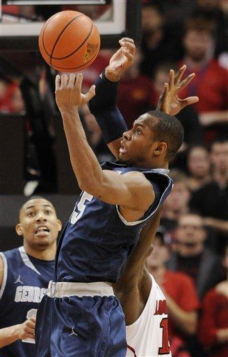 Georgetown's Markel Starks, front, grabs a rebound away from Louisville's Gorgui Dieng during the second half of an NCAA college basketball game Wednesday, Dec. 28, 2011, in Louisville, Ky. Georgetown defeated Louisville 71-68. (AP Photo/Timothy D. Easley)