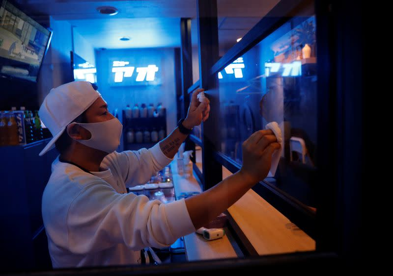 Kazuki Harada, owner of the gay bar New AO, disinfects a plastic panel which was installed to prevent infection, amid the COVID-19 outbreak, at Shinjuku Ni-chome gay district in Tokyo