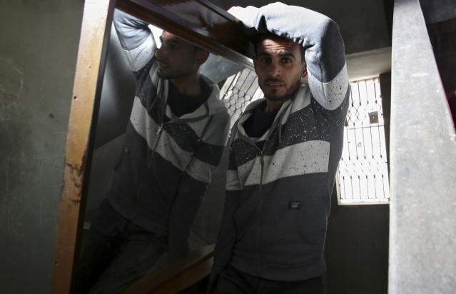 In this April 21, 2019 photo, Palestinian groom Yehiya Taleb, center, move a mirror, part of his wedding furniture, to his apartment in Shati refugee camp, Gaza City. Hundreds of young men in the Gaza Strip have turned to a small industry of lenders to help them pay for their weddings. Taleb got a job working as a waiter at a cafe earning about $180 a month, but that amount was not enough to cover wedding expenses so he took out a $2,000 package through the Farha Project, one of the wedding financing companies. (AP Photo/Adel Hana)