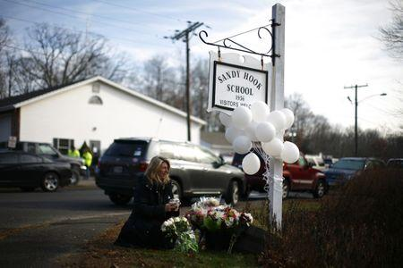 A woman places flowers at a memorial at a sign for Sandy Hook Elementary School in Sandy Hook, Connecticut December 15, 2012. REUTERS/Eric Thayer