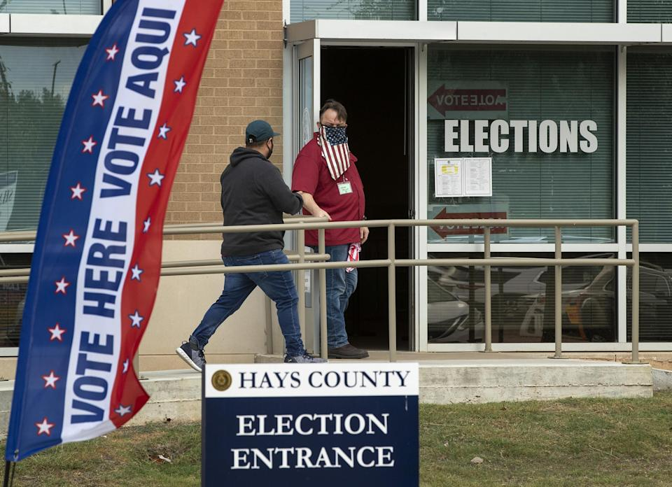 Election clerk Wes Garcia, right, holds the door for a voter Monday at an early voting location at the Hays County Elections Office in San Marcos, Texas. A federal judge late Tuesday ordered that masks be worn in polling places.