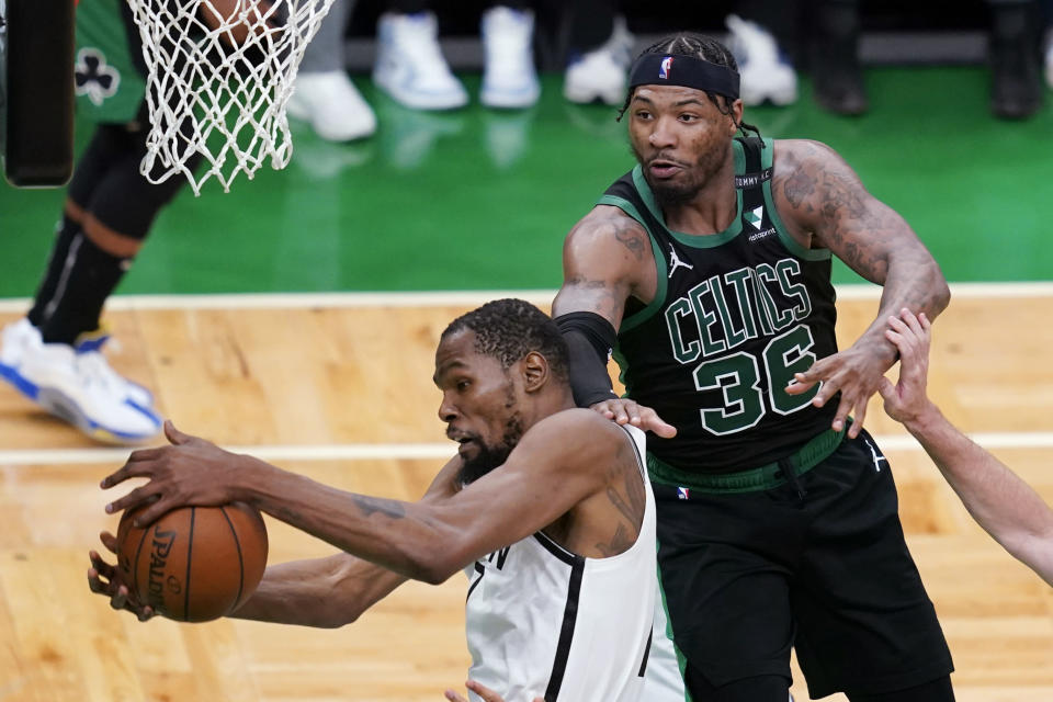 Brooklyn Nets forward Kevin Durant grabs a rebound in front of Boston Celtics guard Marcus Smart (36) during the fourth quarter of Game 3 during an NBA basketball first-round playoff series Friday, May 28, 2021, in Boston. (AP Photo/Elise Amendola)