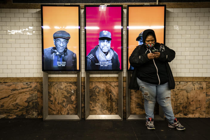 Faces of New York's Metropolitan Transportation Authority employees who died of COVID-19 are displayed at Fulton Street station, Monday, Jan. 25, 2021, in the Manhattan borough of New York. The MTA is honoring its 136 employees who have died from the virus since the pandemic began with a digital memorial at 107 subway stations. (AP Photo/John Minchillo)