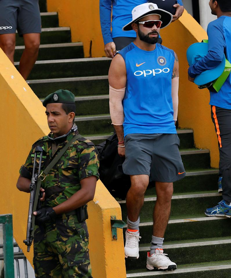 Cricket - Sri Lanka v India - India's Team Practice Session - Galle, Sri Lanka - July 24, 2017 - India's cricket captain Virat Kohli arrives as a Special Task Force (STF) soldier stands guard near India's cricket team dressing room ahead of their first test match. REUTERS/Dinuka Liyanawatte