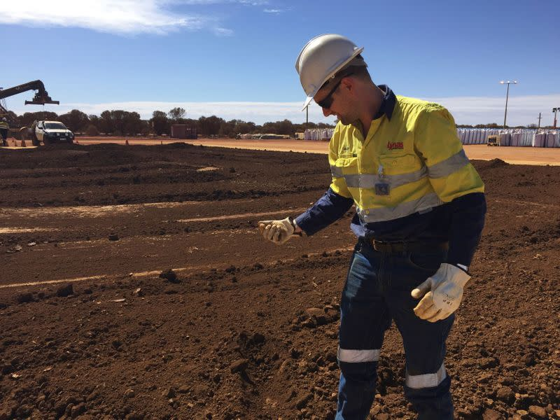 FILE PHOTO: A worker picks up a handful of rare earth concentrate that has been left to dry in the sun before it is packed and shipped to Malaysia for further processing, at Mount Weld, northeast of Perth, Australia