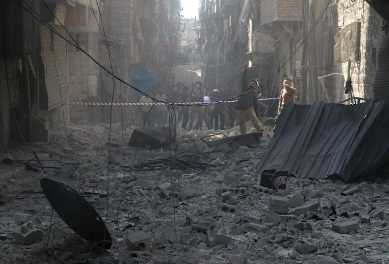 Syrians stand in a street filled with debris following a reported barrel bomb attack by government forces in the northern Syrian city of Aleppo on October 31, 2014 (AFP Photo/Baraa al-Halabi)