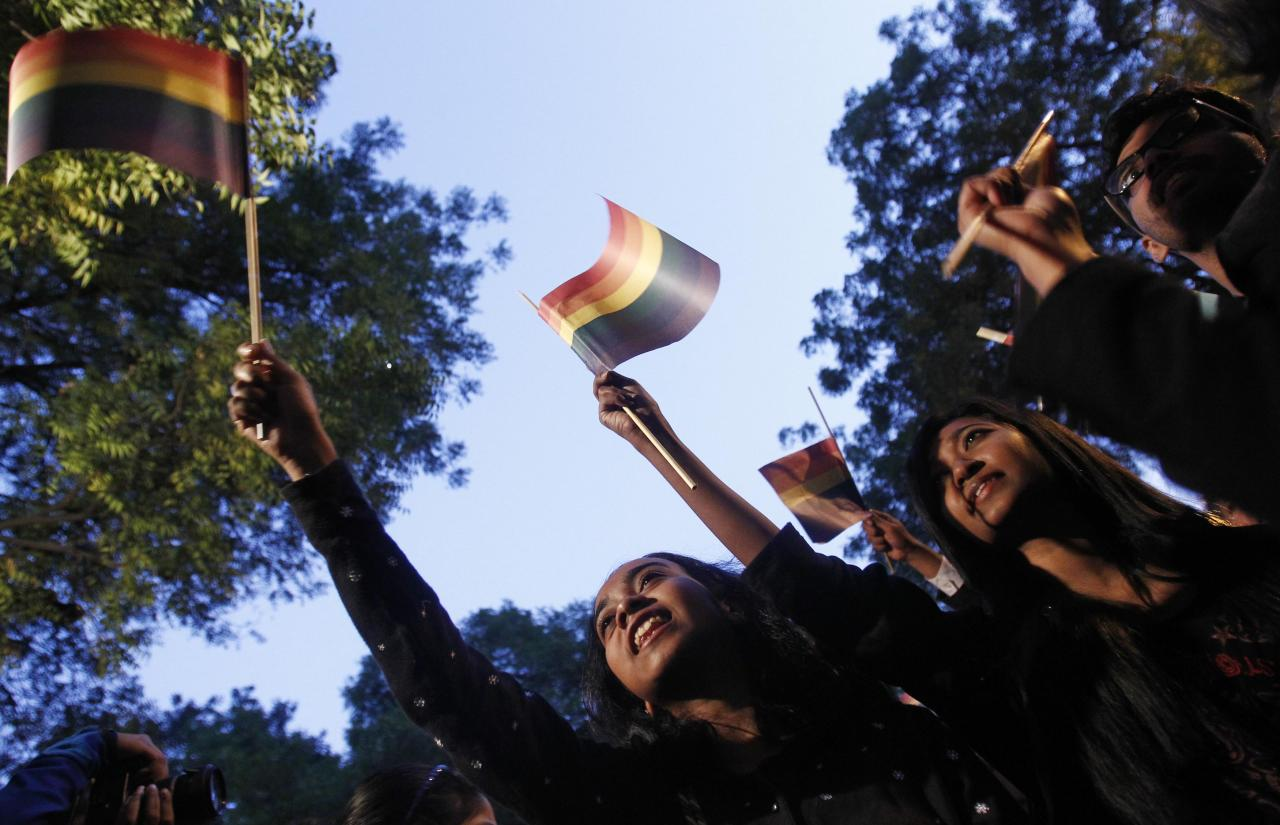 """Gay rights activists wave flags as they attend a protest against a verdict by the Supreme Court in New Delhi December 11, 2013. India's Supreme Court on Wednesday reinstated a ban on gay sex in the world's largest democracy, following a four-year period of decriminalisation that had helped bring homosexuality into the open in the socially conservative country. In 2009 the Delhi High Court ruled unconstitutional a section of the penal code dating back to 1860 that prohibits """"carnal intercourse against the order of nature with any man, woman or animal"""" and lifted the ban for consenting adults. The Supreme Court threw out that decision, saying only parliament could change Section 377 of the penal code, widely interpreted to refer to homosexual sex. Violation of the law can be punished with up to 10 years in jail. REUTERS/Anindito Mukherjee (INDIA - Tags: CRIME LAW SOCIETY)"""