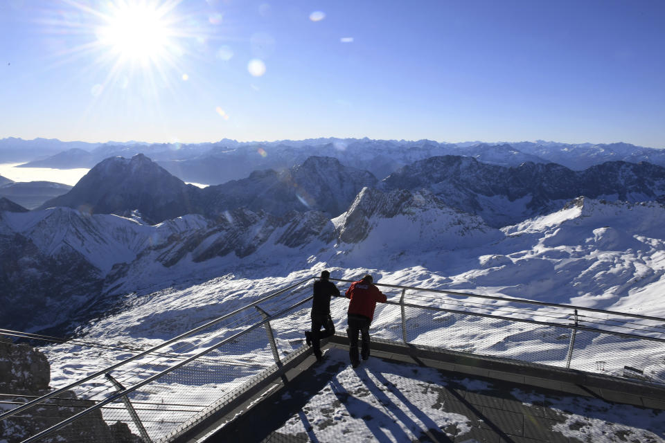 Two employees look out over the closed ski resort at the Zugspitze in Grainau, Germany, Monday, Nov 30, 2020. The skiing areas are prepared but due to the Corona pandemic restrictions skiing is not allowed at the area. (Angelika Warmuth/dpa via AP)