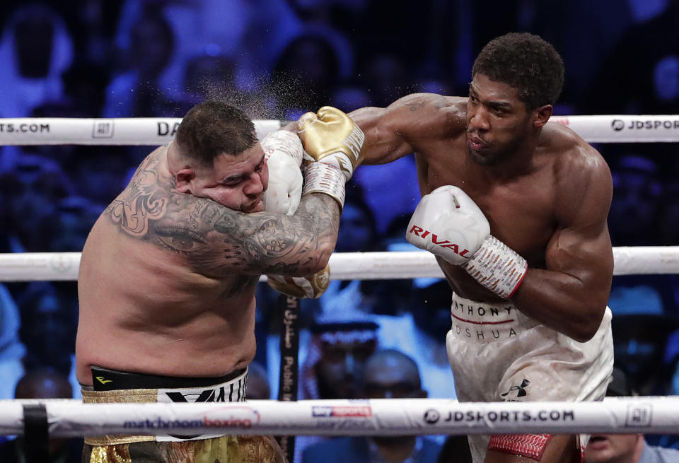 FILE - In this Dec. 8, 2019, file photo, defending champion Andy Ruiz Jr., left, takes a right cross to the face during his fight against Britain's Anthony Joshua in their World Heavyweight Championship contest at the Diriyah Arena, Riyadh, Saudi Arabia. An all-British world heavyweight title showdown between Anthony Joshua and Tyson Fury in 2021 is a step closer. Fury said Wednesday, June 10, 2020, that an agreement has been reached with Joshua's camp on a two-fight deal between the current holders of the heavyweight belts. (AP Photo/Hassan Ammar, File)