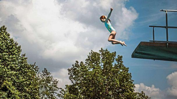 PHOTO: Abby Swank, 10, of Robinson, leaps off a diving board at the pool at Settlers Cabin Park, Thursday, July 18, 2019, in Robinson, Pa. (Alexandra Wimley/AP)