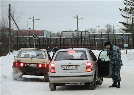 Police officers check cars on the road in front of the Penal Colony 7, where Mikhail Khodorkovsky was held at, in the village of Segezha near the Finnish border, 300 km (200 miles) south of the Arctic Circle, December 20, 2013. REUTERS/Tatyana Makeyeva