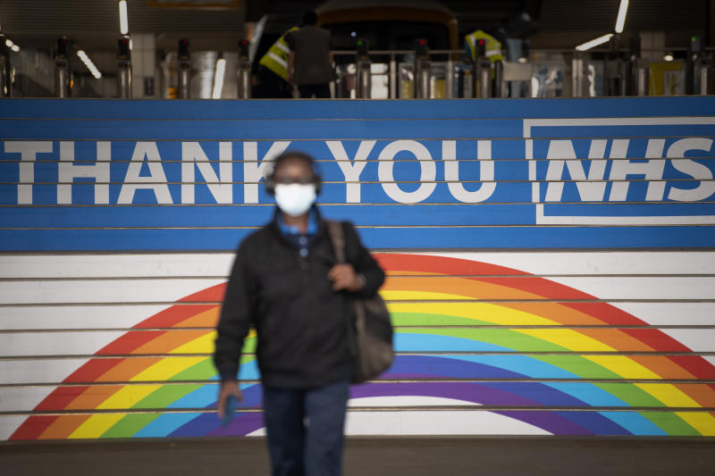 A commuter wearing a mask walks past a thank you message for the NHS at Cannon Street station in London, after the introduction of measures to bring the country out of lockdown.