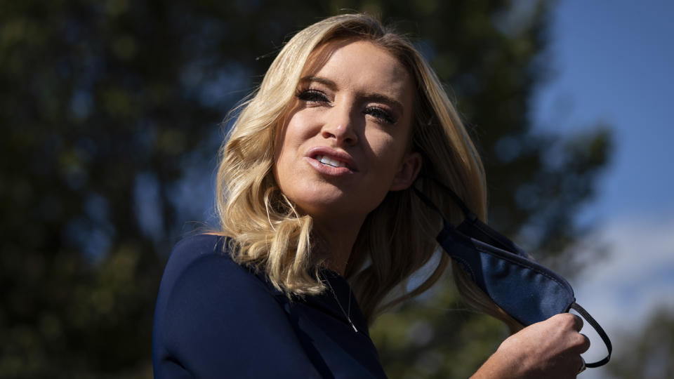 White House press secretary Kayleigh McEnany takes off her face covering before speaking with reporters outside the West Wing on Friday. (Drew Angerer/Getty Images)