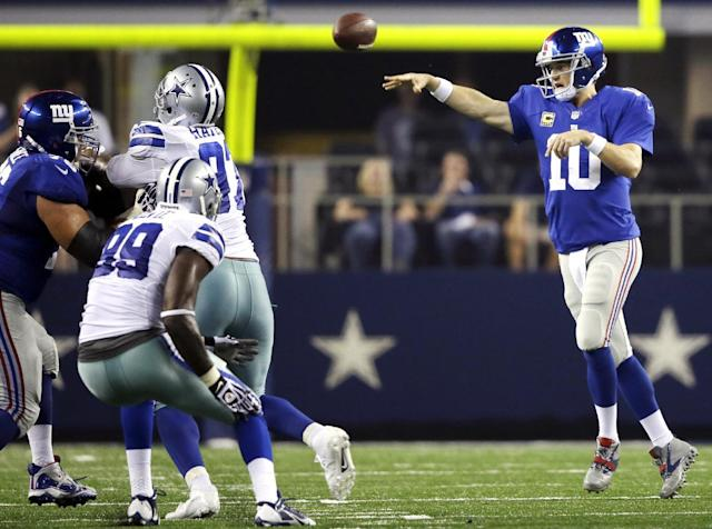 New York Giants quarterback Eli Manning (10) throws an interception to Dallas Cowboys cornerback Brandon Carr (39) who returned the ball 49 yards for a touchdown during the second half of a NFL football game, Sunday, Sept. 8, 2013, in Arlington, Texas. (AP Photo/Tony Gutierrez)