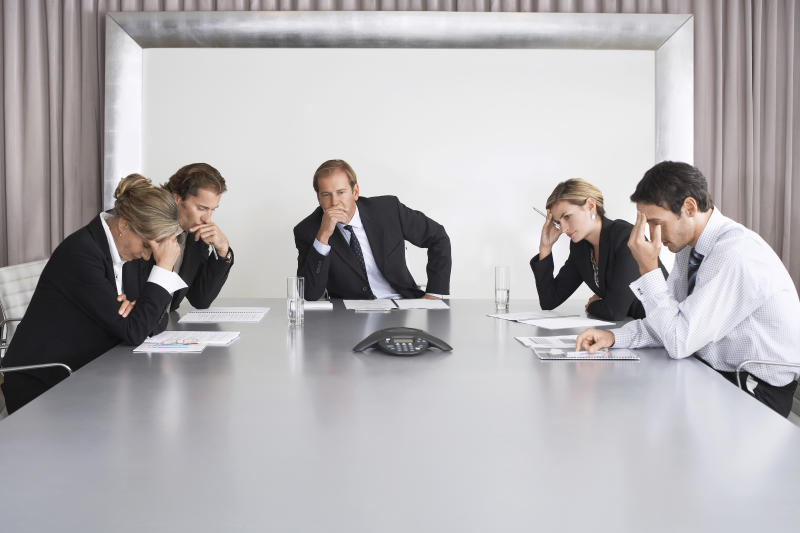 People in business suits sitting around a conference table looking uncomfortable.