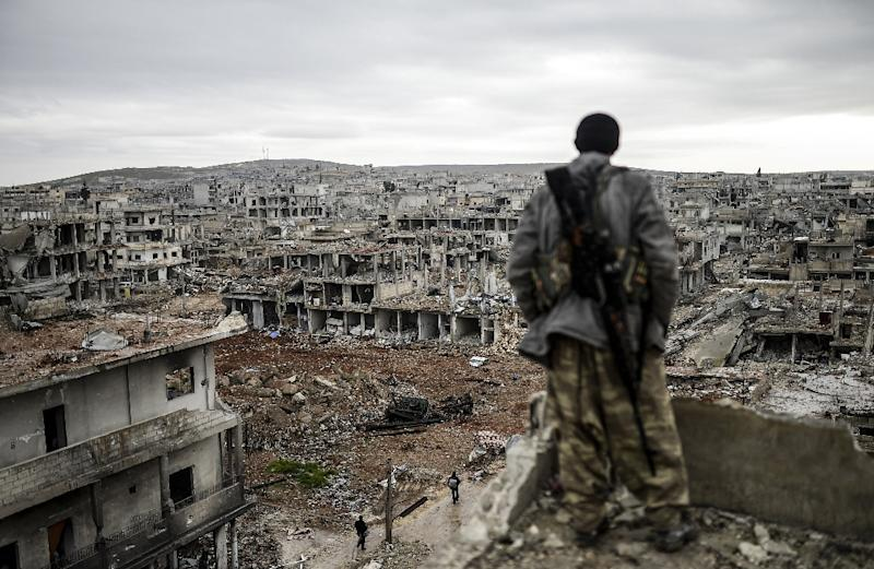 Musa, a 25-year-old Kurdish marksman, looks at the destroyed Syrian town of Kobane on January 30, 2015 (AFP Photo/Bulent Kilic)