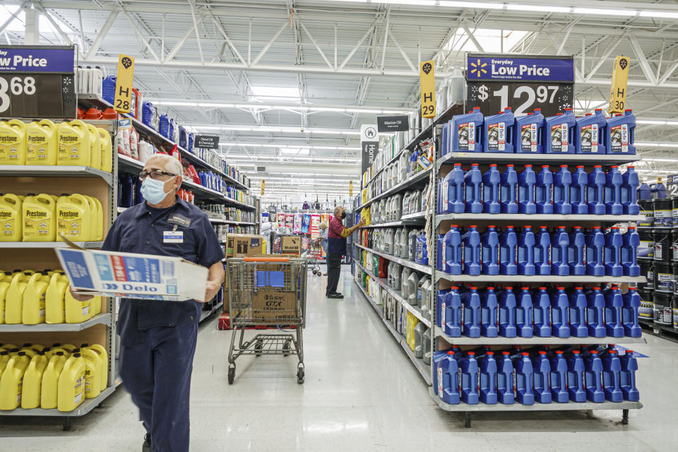 Walmart discount department store employees stocking shelves with engine oil in Miami, Florida. (Photo by: Jeffrey Greenberg/Universal Images Group via Getty Images)
