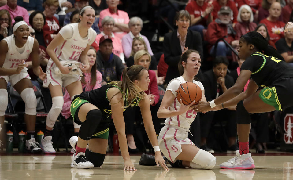 Oregon's Ruthy Hebard, right, and Sabrina Ionescu try to steal the ball from Stanford's Lacie Hull (24) during the first half of an NCAA college basketball game Monday, Feb. 24, 2020, in Stanford, Calif. (AP Photo/Ben Margot)