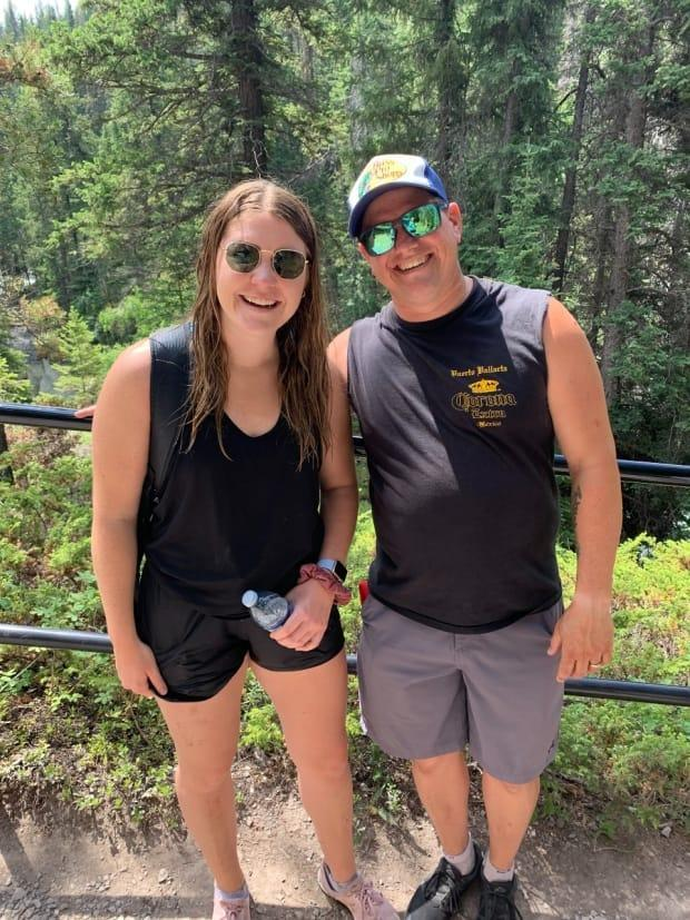 Katelyn Jones, who fell into the Maligne River, poses with Phil James, who came to her rescue. (Submitted by Katelyn Jones - image credit)