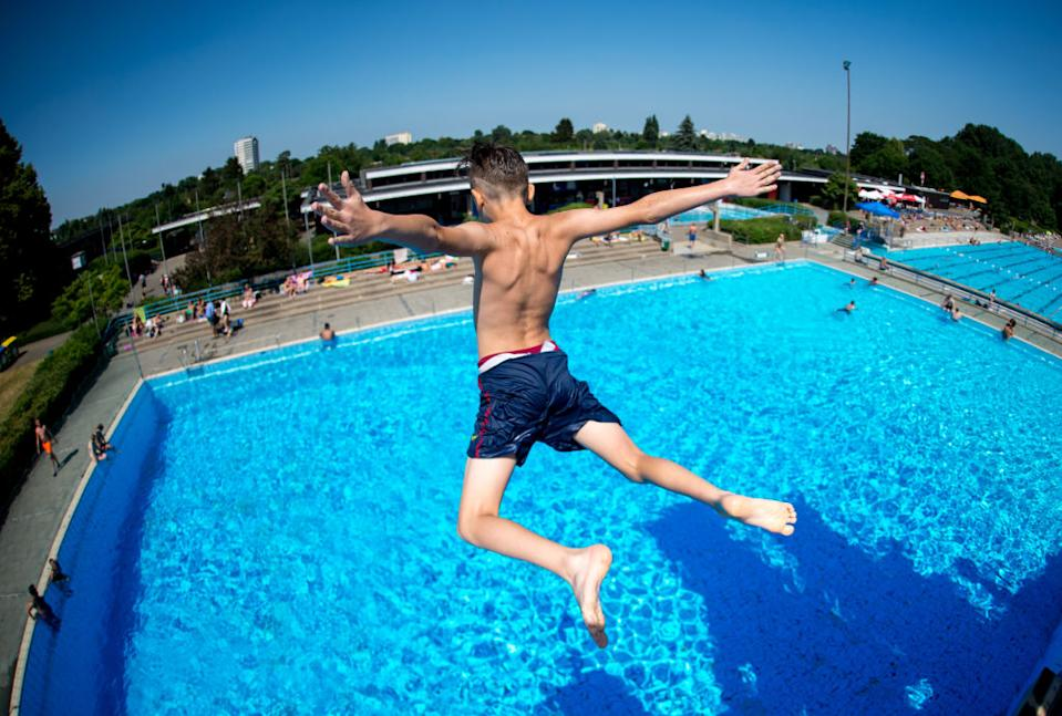 07 June 2018, Germany, Hanover: A youth jumps from a diving tower at the Lister Freibad open air swimming pool. (Photo taken using fish-eye lens) Photo: Hauke-Christian Dittrich/dpa (Photo by Hauke-Christian Dittrich/picture alliance via Getty Images)