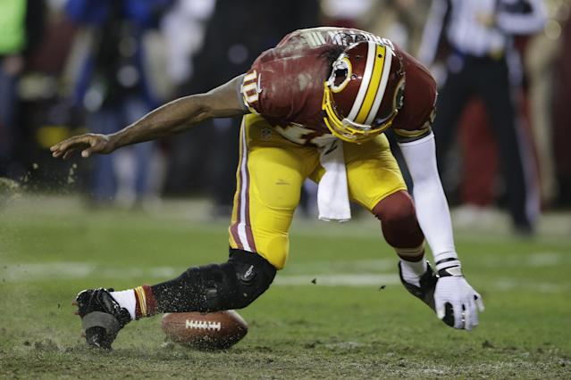 Washington Redskins quarterback Robert Griffin III twists his knees as he reaches for a loose ball after a low snap during the second half of an NFL wild card playoff football game against the Seattle Seahawks in Landover, Md., Sunday, Jan. 6, 2013. (AP Photo/Matt Slocum)