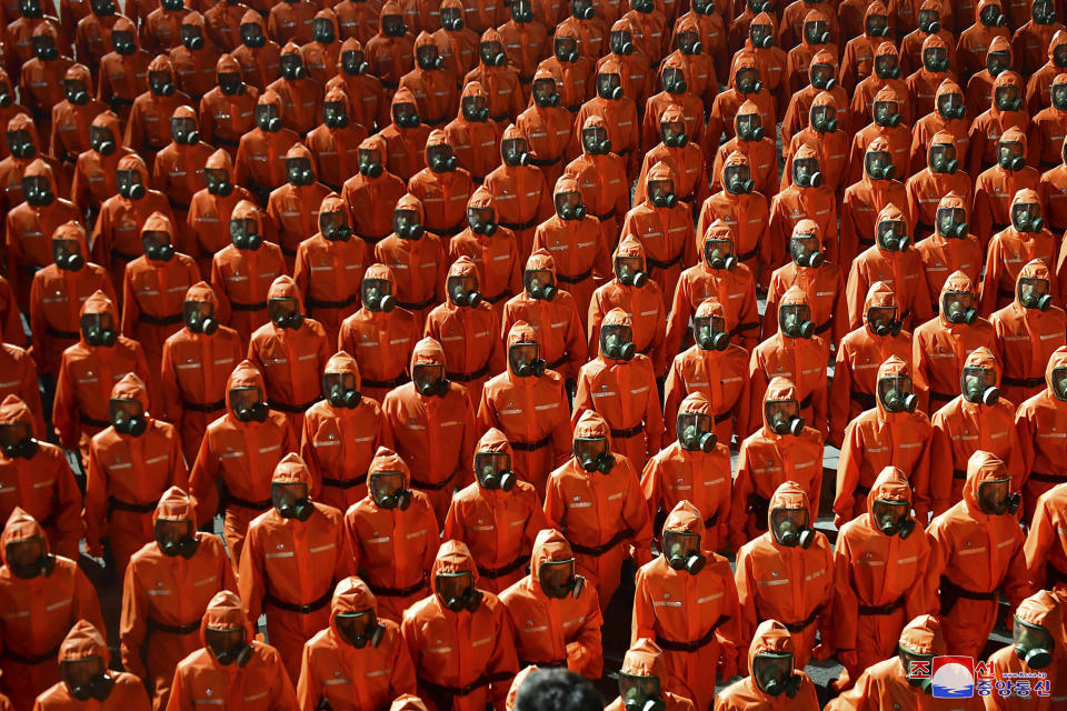 """In this photo provided by the North Korean government, North Korean troops wearing gas masks and bright red suits parade during a celebration of the nation's 73rd anniversary that was overseen by leader Kim Jong Un, at Kim Il Sung Square in Pyongyang, North Korea, early Thursday, Sept. 9, 2021. Independent journalists were not given access to cover the event depicted in this image distributed by the North Korean government. The content of this image is as provided and cannot be independently verified. Korean language watermark on image as provided by source reads: """"KCNA"""" which is the abbreviation for Korean Central News Agency. (Korean Central News Agency/Korea News Service via AP)"""