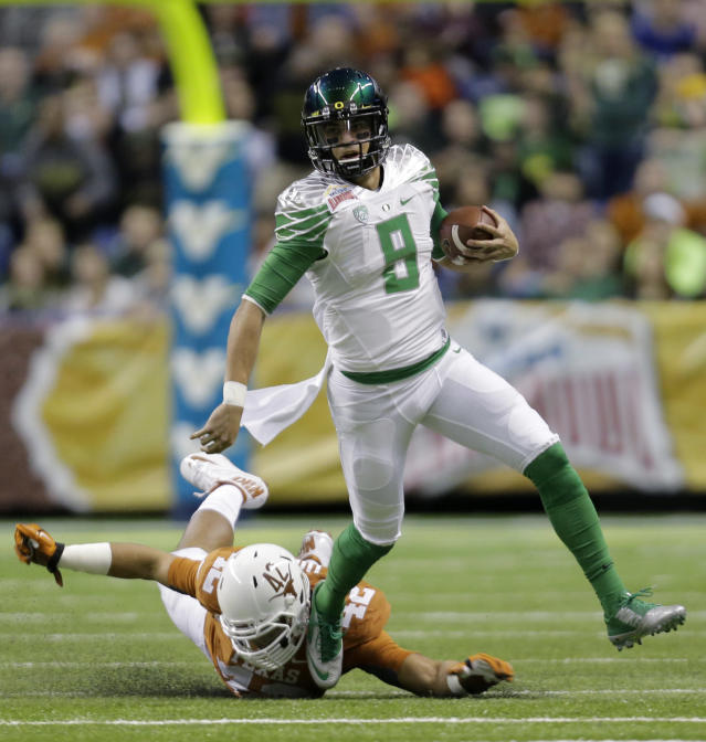 Oregon's Marcus Mariota (8) is pursued by Texas' Caleb Bluiett (42) during the first quarter in the Valero Alamo Bowl NCAA college football game, Monday, Dec. 30, 2013, in San Antonio. (AP Photo/Eric Gay)