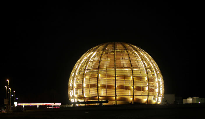 """FILE - In this March 30, 2010 file picture the globe of the European Organization for Nuclear Research, CERN, is illuminated outside Geneva, Switzerland. With COVID-19, the race to space and climate change high on many minds, a new """"do tank"""" in Geneva bankrolled by the Swiss government is gearing up to develop long-term projects like creating a global court for scientific disputes and a Manhattan Project-style effort to rid excess carbon from the atmosphere. (AP Photo/Anja Niedringhaus, file)"""
