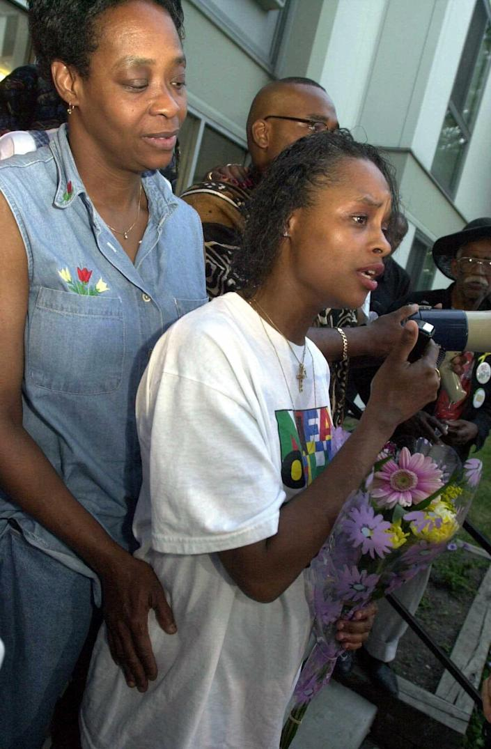 Tracey Bradley, right, mother of two missing girls, Tionda, 10, and Diamond, 3, speaks to the crowd gathered for the nightly prayer vigil outside their apartment complex July 14, 2001, in Chicago. She is held by her mother, Mary Bradley-Hunt.