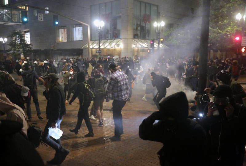 Police used tear gas and stun grenades on a group of protesters in downtown Portland on Tuesday night, June 2, 2020.  Protests continued for a sixth night in Portland, demonstrating over the death of Minneapolis resident George Floyd. Floyd died after being restrained by Minneapolis police officers on May 25. (Brooke Herbert/The Oregonian via AP)