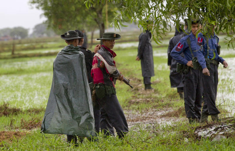 In this June 5, 2013 photo, Myanmar Navy officers stand guard in a paddy confiscated from farmers in 1992 by the Myanmar security forces in Dala, southeast of Yangon Myanmar. Despite sweeping reforms since a quasi-civilian government was installed two years ago, authorities not only have broad powers to seize land in the name of national interest, but to arrest, try and imprison small-scale farmers and political activists who stand up in protest. (AP Photo/Gemunu Amarasinghe)