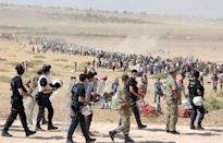 Turkish policemen and soldiers walk as Syrian Kurds wait behind the border fence to cross into Turkey near the southeastern town of Suruc in Sanliurfa province, September 19, 2014. REUTERS/Stringer