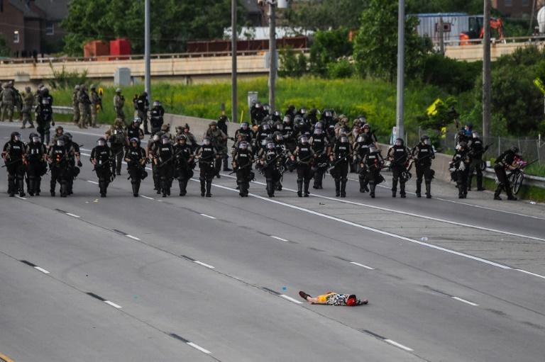 A demonstrator lies on the highway in front of the police line during a protest over the death of George Floyd on May 31, 2020 in Minneapolis
