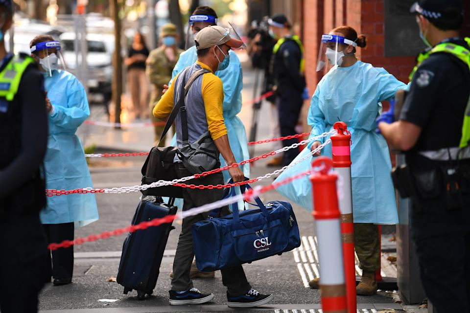 A return traveller (centre) exits a Skybus upon arriving to the Intercontinental quarantine hotel in Melbourne. Source: AAP