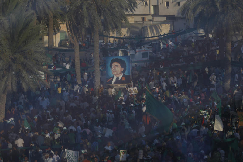 """In this photo taken on a government-organized tour, a poster of Libyan Leader Moammar Gadhafi is seen during a rally through a glass window, in the town of Ajaylat, roughly 80km (50 miles) west of Tripoli, Libya, Thursday, July 14, 2011. In Moscow, Thursday a Russian newspaper quoted the Kremlin's special envoy to Libya as saying Moammar Gadhafi has threatened to blow up Tripoli if the Libyan capital falls into rebel hands. Mikhail Margelov told the Izvestia newspaper that Libyan Prime Minister Al-Baghdadi al-Mahmoudi recently told him, """"If the rebels seize the city, we will deluge it with missiles and blow it up.""""  (AP  Photo/Tara Todras-Whitehill)"""
