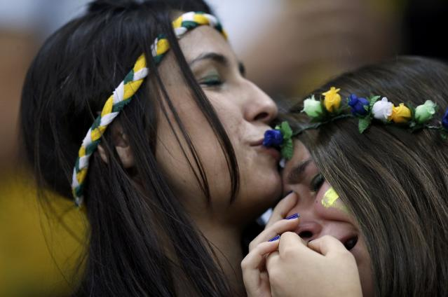 A fan of Brazil is consoled after they lost their 2014 World Cup third-place playoff against the Netherlands at the Brasilia national stadium in Brasilia July 12, 2014. REUTERS/Ueslei Marcelino (BRAZIL - Tags: SOCCER SPORT WORLD CUP)