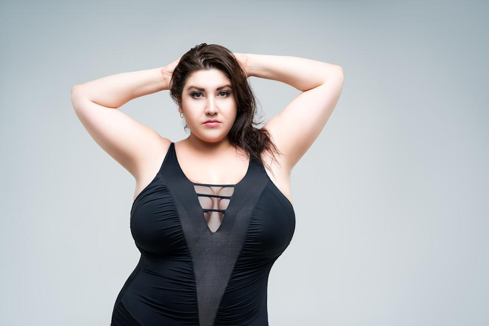 Sexy plus size fashion model in black one-piece swimsuit, woman in lingerie on gray background, body positive concept