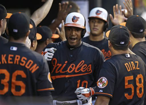 Baltimore Orioles' Adam Jones, center, high-fives teammates in the dugout after hitting a three-run home run in the third inning of a baseball game against the Toronto Blue Jays, Friday, July 12, 2013, in Baltimore. (AP Photo/Patrick Semansky)
