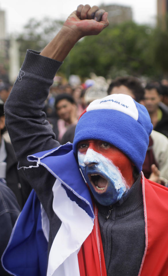A supporter of Paraguay's President Fernando Lugo, whose face is painted with the colors of Paraguay's national flag, protests against Lugo's impeachment trial, outside Parliament, in Plaza de Armas, Asuncion, Paraguay, Friday, June 22, 2012. Paraguayan lawmakers voted Thursday to impeach Lugo for his role in for his role in a deadly clash involving landless farmers and police. Lugo's trial was to begin Friday in Paraguay's Senate. (AP Photo/Jorge Saenz)