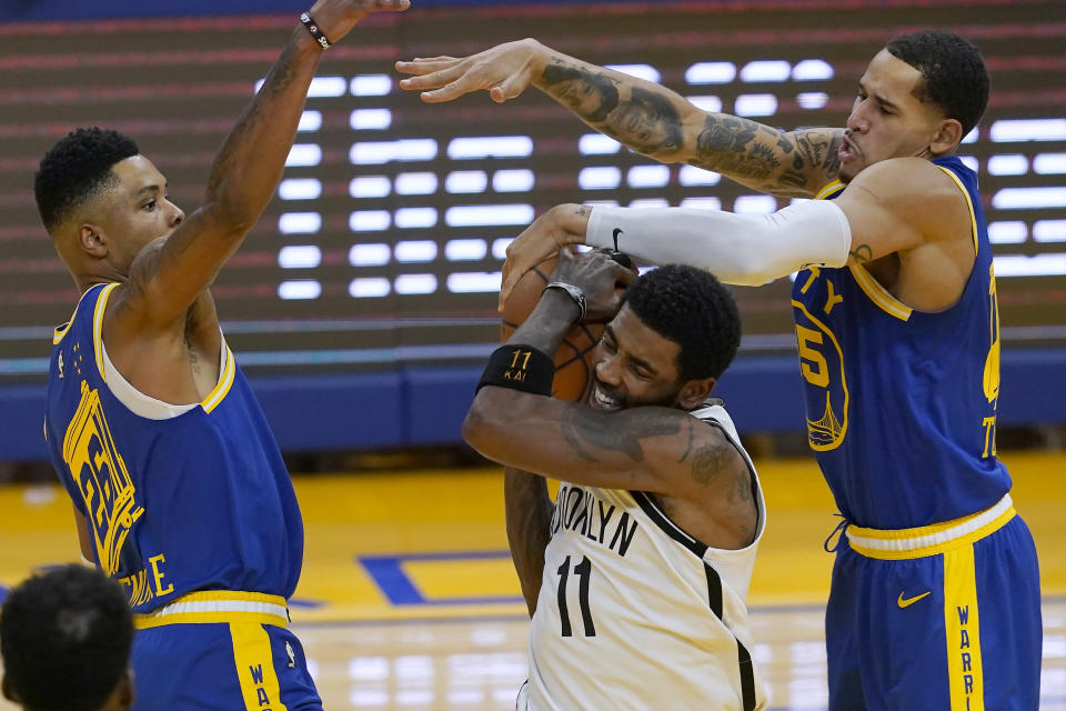 Brooklyn Nets guard Kyrie Irving (11) is defended by Golden State Warriors forwards Kent Bazemore, left, and Juan Toscano-Anderson during the first half of an NBA basketball game in San Francisco, Saturday, Feb. 13, 2021. (AP Photo/Jeff Chiu)
