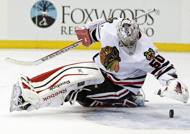 Chicago Blackhawks goalie Corey Crawford prepares to smother the puck after it rolled out from under him during the second period of an NHL hockey game against the New York Rangers at Madison Square Garden in New York, Thursday, Feb. 27, 2014. (AP Photo/Kathy Willens)