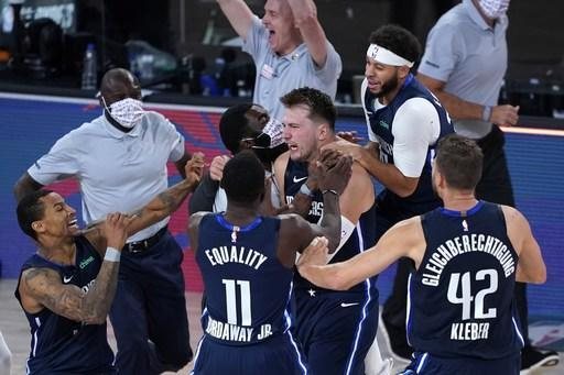 Dallas Mavericks' Luka Doncic, center, celebrates with teammates after making a game-winning 3-point basket against the Los Angeles Clippers during overtime of an NBA basketball first round playoff game Sunday, Aug. 23, 2020, in Lake Buena Vista, Fla. The Mavericks won 135-133 in overtime. (AP Photo/Ashley Landis, Pool)