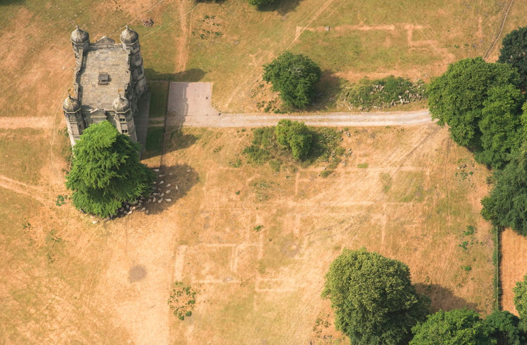 <p>The large building on the left is a gatehouse built in 1557, during the reign of Elizabeth I, while the lighter lines in the centre are where the dying grass has revealed the buried foundations of Tixall Hall in Staffordshire (Historic England) </p>