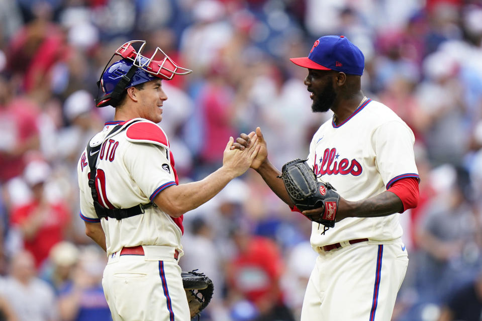 Philadelphia Phillies pitcher Enyel De Los Santos, right, and catcher J.T. Realmuto celebrate after the Phillies won a baseball game against the New York Yankees, Sunday, June 13, 2021, in Philadelphia. (AP Photo/Matt Slocum)